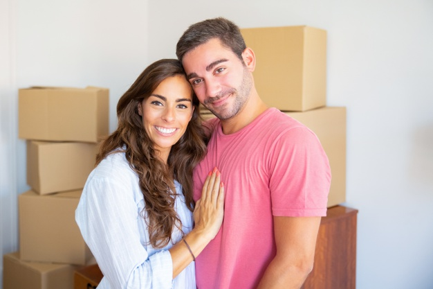 happy-beautiful-hispanic-couple-standing-among-carton-boxes-their-new-flat-hugging-looking-camera_74855-9952