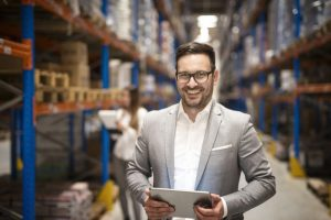 portrait-successful-middle-aged-manager-businessman-holding-tablet-computer-large-warehouse-organizing-distribution_342744-1548